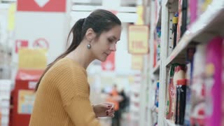 Young beautiful woman standing in front of shelves with household chemicals, holding one and try to choose. 4K