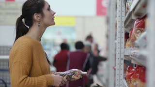 Young beautiful woman standing in front of shelves with pasta, holding one and try choose something in supermarket. 4K