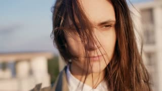 Young beautiful woman standing on the roof at the sunset, her long dark hair blowing wind. slow motion.