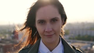 Young beautiful woman standing on the roof of high-rise building at sunset looking at the camera. close-up. Slow mo