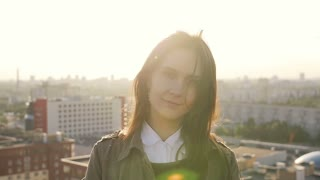 Young beautiful woman standing on the roof of high-rise building at sunset looking at the camera. Slow mo