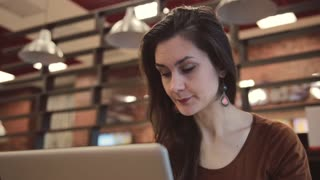 Young brunette girl working on laptop in cafe.