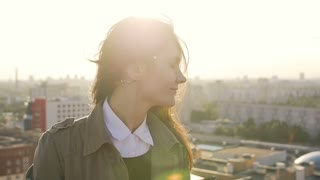 young brunette woman standing on the roof at sunset turns the head and her hair is blowing by the wind. slow mo