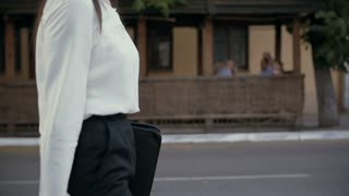 Young businesswoman walking in old city. slow mo