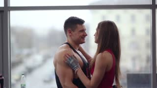 Young couple express love to each other. Sporty man and woman in love hug and kiss standing near the window.