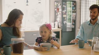 Young couple feeding their cute blond daughter breakfast in the morning. Slow motion, Steadicam shot