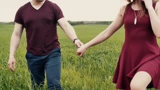 Young couple in love walking through long green grass. They are holding hands. Slow mo, steadicam shot