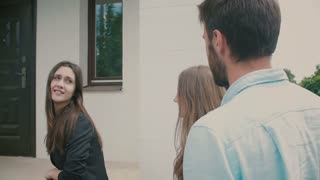 Young couple is following a chatty brunette to the front door of a big white house. Slow motion, Steadicam shot