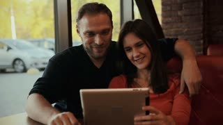 Young couple using digital tablet computer. cafe