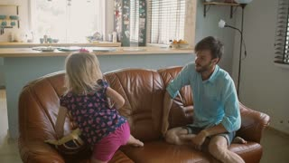 Young dad is playing with his cute daughter on the sofa, pillow fighting her and tickling. Slow mo, Steadicam shot