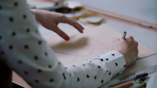 Young designer sitting at the table and draw layout of shoe on papers pattern. Close-up, back view. 4K