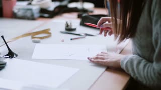 Young designer sitting at the table and drawing the sketch of blue shoes. Woman erase on paper. Side view. 4K
