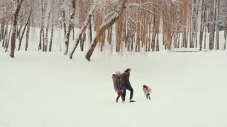 Young family playing and having fun in the snow