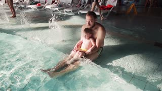 Young father and son in aquapark. Man with his cute baby boy sitting in a swimming pool and enjoying the waves