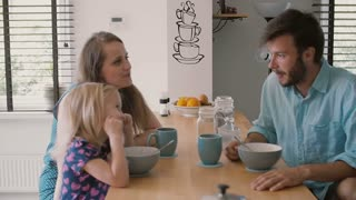 Young father is looking at his wife and daughter at the kitchen table during breakfast. Slow motion, Steadicam shot