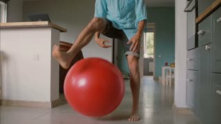 Young father is playing basketball with his little daughter with a big red gym balloon in the living room. Slow motion