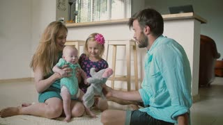 Young father is playing with his little daughter and baby son, while his wife is holding the baby. Slow motion