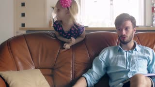 Young fatheris sitting on the sofa and talking to someone while his daughter is smiling in the back. 4k