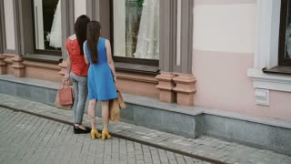 Young girls friends standing near shop window with wedding dresses and discuss. slow mo
