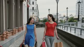 Young girls friends walking after shopping with purchases in bags, talking and laughing. slow mo stedicam shot