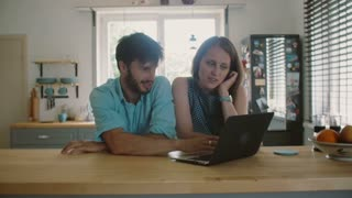 Young good-looking couple is sitting at the kitchen table looking at the computer and talking. Slow motion