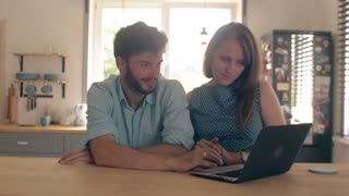 Young good-looking couple is talking at the kitchen table looking at the laptop. 4k