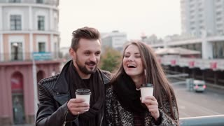 Young handsome man and a beautiful young brunette girl laughing emotionally, having takeaway coffee. Slow mo