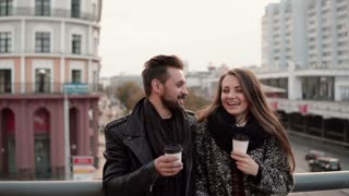 Young handsome man and a beautiful young brunette girl laughing emotionally, having takeaway coffee.