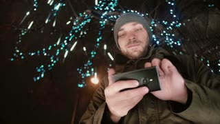 young handsome man using smartphone at Christmas night standing under a tree decorated with sparkling lights