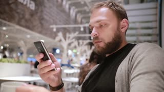 Young handsome man with a beard drinking coffee or tea, using his smartphone in a cafe. Modern technology.