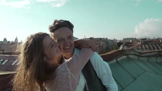 young happy beautiful stylish couple hugging gently on the roof at sunset