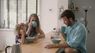 Young happy family is having peaceful breakfast in the morning. Slow motion, Steadicam shot