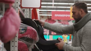 Young man choosing the item on the shelves in the store, wants to bye baby car chair. 4K