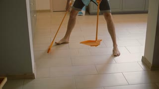 Young man, husband is goofing around with yellow broomstick while sweeping floor in the kitchen. Slow mo, Steadicam shot