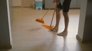 Young man, husband is sweeping the kitchen floor carefully with yellow broomstick and scoop. Slow motion, Steadicam shot