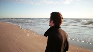 young man in a black coat is walking along sea shore with sun shining at his back.