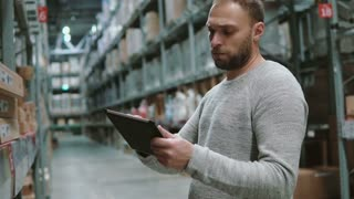 Young man using digital tablet in warehouse, checking goods at supermarket. 4K