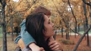 young mother holds on shoulders cute little boy, little boy hugs her near bird feeders in amazing autumn park 4k