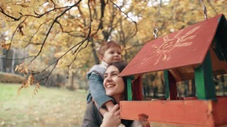 young mother holds on shoulders cute little boy, little boy hugs kisses her near bird feeders in amazing autumn park 4k