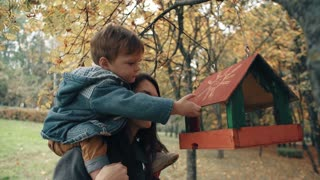 young mother holds on the shoulders a cute little boy, the boy puts food in the bird feeder in an amazing autumn park 4k