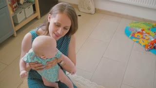 Young mother is holding her precious baby and smiling at him sitting on the kitchen floor. Slow motion