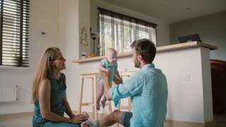 Young mother is sitting on the kitchen with her husband watching him lifting their baby up high. Slow motion