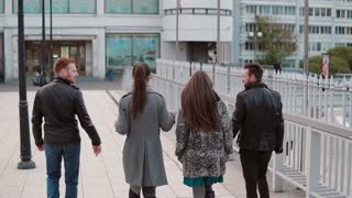 Young people on a bridge. Two pretty girls and two handsome young men talk on the go. Slow mo, back view, steadicam shot