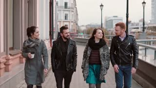 Young people walk in the city. Two pretty girls and two handsome young men talk on the go. Slow mo, steadicam shot