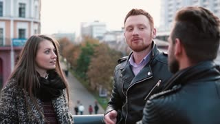 Young pretty girl and a red-haired man talk to another man standing near a bridge railing. Slow mo, steadicam shot