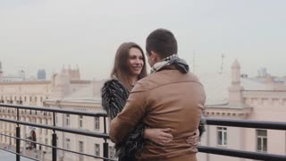 Young pretty man and woman in love on a roof of a house talk and hug. A beautiful view of buildings. Steadicam shot