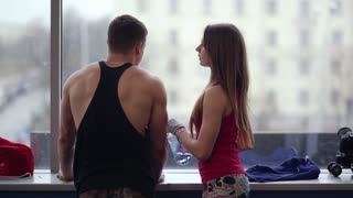 Young sporty man and woman standing near the window in a sport club talking. Woman is drinking water after workout