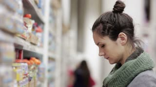 Young woman chooses baby food in the supermarket
