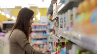 Young woman chooses baby toys in the supermarket