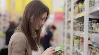Young woman chooses canned food in the store